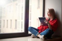 Retrato de una chica joven que lee un eBook en la ventana Imágenes de archivo libres de regalías
