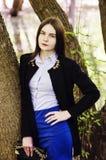 Retrato de una chica joven que presenta cerca de un árbol en el banco de la charca fotos de archivo