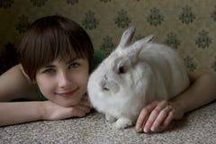 Retrato de una chica joven que sostiene un conejito afuera Imagen de archivo libre de regalías