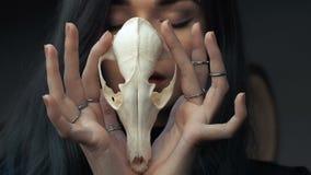 Retrato de una chica joven que sostiene un cráneo misterioso en las manos de un zorro Pelo largo pintado almacen de metraje de vídeo