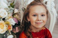 Retrato de una chica joven sonriente en un vestido rojo y con un peinado hermoso imágenes de archivo libres de regalías