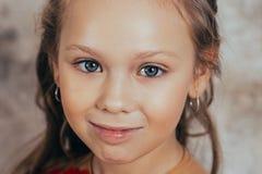 Retrato de una chica joven sonriente en un vestido rojo y con un peinado hermoso Tiro del estudio fotografía de archivo libre de regalías