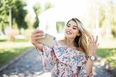 Retrato de una chica joven sonriente que hace el teléfono de la foto del selfie en parque Foto de archivo