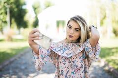 Retrato de una chica joven sonriente que hace el teléfono de la foto del selfie en parque Fotografía de archivo