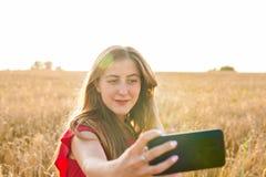 Retrato de una chica joven sonriente que hace la foto del selfie en el campo Fotos de archivo libres de regalías