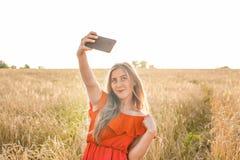 Retrato de una chica joven sonriente que hace la foto del selfie en el campo Imagen de archivo libre de regalías