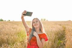Retrato de una chica joven sonriente que hace la foto del selfie en el campo Fotografía de archivo libre de regalías