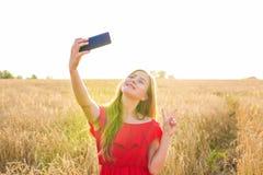 Retrato de una chica joven sonriente que hace la foto del selfie en el campo Imágenes de archivo libres de regalías
