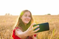 Retrato de una chica joven sonriente que hace la foto del selfie en el campo Fotografía de archivo