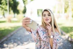Retrato de una chica joven sonriente que hace la foto del selfie en parque Foto de archivo libre de regalías