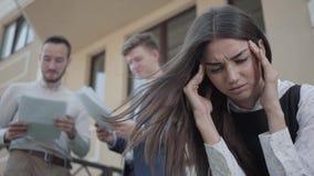 Retrato de una chica joven trastornada linda con un dolor de cabeza Una mujer que lleva a cabo su cabeza Dos colegas con los docu metrajes