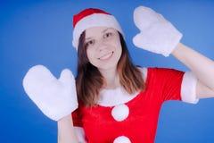 Retrato de una chica joven vestida como Santa Claus en un fondo azul ¡Feliz Año Nuevo y Feliz Navidad! fotografía de archivo