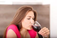 Retrato de una chica joven y de un vino rojo Fotos de archivo libres de regalías