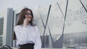 Retrato de una chica riendo usando un smartphone. Mujer muy joven con su teléfono móvil en el parque de la ciudad almacen de metraje de vídeo