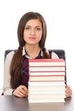 Retrato de una colegiala con una pila de libros que se sientan en su d Imagenes de archivo