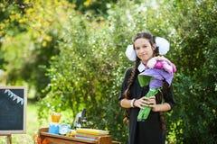 Retrato de una colegiala joven hermosa con la manzana roja en los libros en un uniforme escolar festivo Fotos de archivo