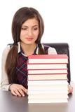 Retrato de una colegiala que mira a una pila de libros imagen de archivo