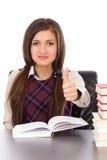 Retrato de una colegiala que se sienta en su escritorio con un libro abierto a Imagenes de archivo