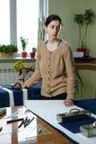 Retrato de una costurera de la mujer joven en un estudio casero Miradas appraisingly en el cliente Llevar a cabo un par de tijera fotos de archivo libres de regalías