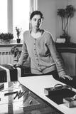 Retrato de una costurera de la mujer joven en un estudio casero Miradas appraisingly en el cliente Llevar a cabo un par de tijera fotografía de archivo