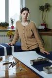 Retrato de una costurera de la mujer joven en un estudio casero Miradas appraisingly en el cliente Llevar a cabo un par de tijera imagen de archivo libre de regalías