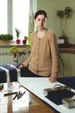 Retrato de una costurera de la mujer joven en un estudio casero Miradas appraisingly en el cliente Llevar a cabo un par de tijera foto de archivo