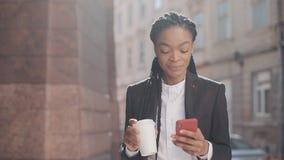 Retrato de una empresaria afroamericana joven en un traje, caminando alrededor de la ciudad, del café de consumición y de usar almacen de metraje de vídeo