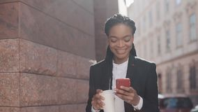 Retrato de una empresaria afroamericana joven en un traje, colocándose en el fondo de la calle, café de consumición y almacen de video