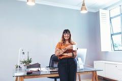 Retrato de una empresaria alegre en oficina imagenes de archivo