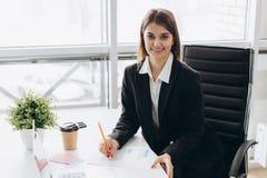 Retrato de una empresaria alegre que se sienta en la tabla en oficina y que mira la cámara imagenes de archivo