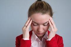 Retrato de una empresaria en una chaqueta roja con dolor de cabeza Foto de archivo libre de regalías