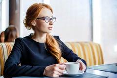 Retrato de una empresaria hermosa joven que goza del café en un café acogedor y que mira hacia fuera la ventana Fotografía de archivo