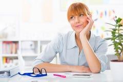 Retrato de una empresaria hermosa joven que sienta su escritorio y pensamiento Foto de archivo