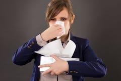 Retrato de una empresaria joven con la gripe que sopla su nariz imagenes de archivo