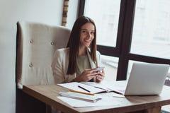 Retrato de una empresaria joven que se sienta con su ordenador portátil en la oficina imagen de archivo libre de regalías