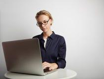 Retrato de una empresaria seria que usa el ordenador portátil en oficina Fotos de archivo