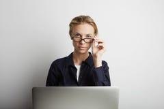 Retrato de una empresaria seria que usa el ordenador portátil en oficina Imagen de archivo