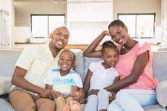 Retrato de una familia de cuatro miembros que ve la TV Imágenes de archivo libres de regalías
