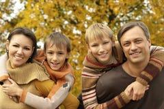 Familia agradable que se relaja en otoño imagenes de archivo