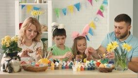 Retrato de una familia feliz con dos niños que dibujan los huevos de Pascua almacen de video