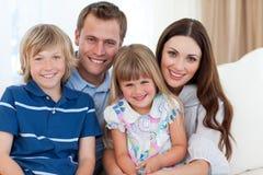 Retrato de una familia feliz en el sofá Foto de archivo