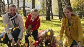 Retrato de una familia feliz en un parque del otoño Los padres y los niños lanzan las hojas anaranjadas en el aire almacen de video