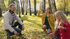 Retrato de una familia feliz en un parque del otoño Los padres y los niños lanzan las hojas anaranjadas en el aire metrajes