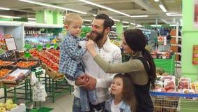 Retrato de una familia feliz grande en el supermercado Compras y concepto de la gente metrajes