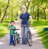 Retrato de una familia feliz - padre e hijo que montan en bicicleta en el parque Fotos de archivo