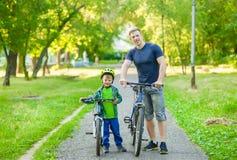 Retrato de una familia feliz - padre e hijo que montan en bicicleta en el parque fotos de archivo libres de regalías