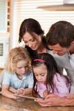 Retrato de una familia feliz usando un ordenador de la tablilla junto Fotos de archivo