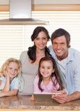 Retrato de una familia sonriente usando un ordenador de la tablilla junto Fotografía de archivo libre de regalías
