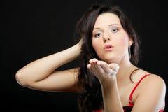 Retrato de una hembra joven linda que sopla un beso hacia Foto de archivo