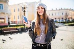 Retrato de una música que escucha de la muchacha feliz en línea con los auriculares inalámbricos de un smartphone en la calle en  Imágenes de archivo libres de regalías